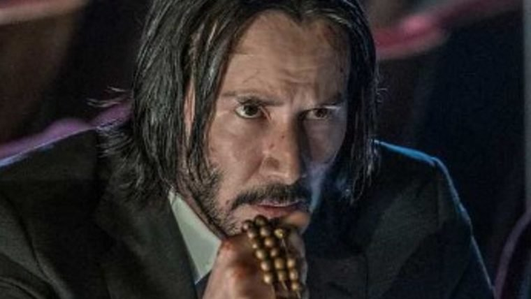 John Wick segura um terço em foto do novo filme