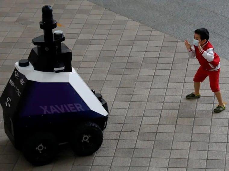 Criança brinca perto do robô Xavier
